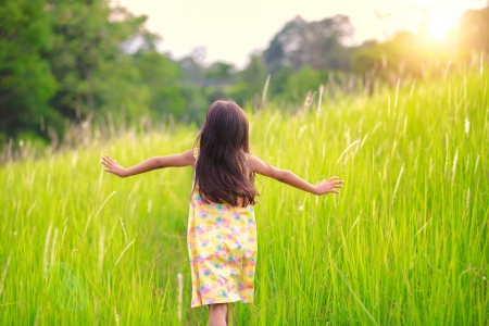 run woman: Happy little girl running on meadow Stock Photo