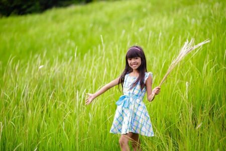 Little asian girl with open arms against green meadow, Outdoor portrait photo