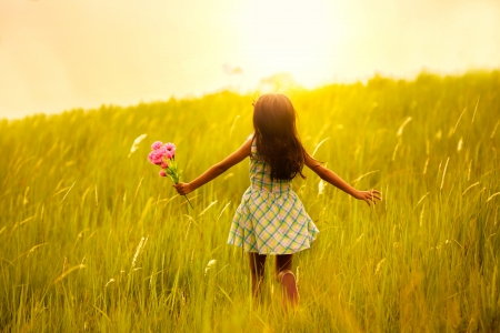 women children: Little girl running on meadow with sunset Stock Photo