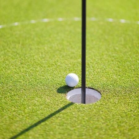 カップの唇にゴルフ ・ ボール 写真素材