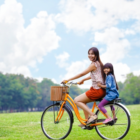 andando en bicicleta: Madre e hija de una bicicleta de ciclismo en el parque