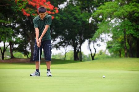 teen golf: Adolescente, joven jugador de golf putting green Foto de archivo