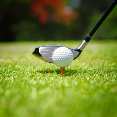 golf equipment: Golf ball on tee in front of driver