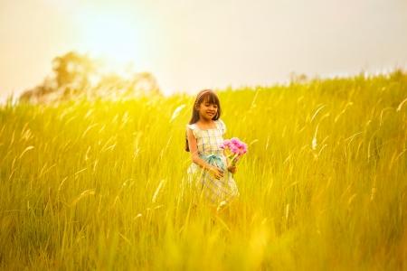 niÑos contentos: Niña en el prado con la puesta del sol