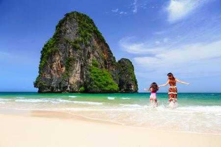 travel family: Familia asi�tica feliz divertirse en ejecuci�n de playa y saltar en la playa