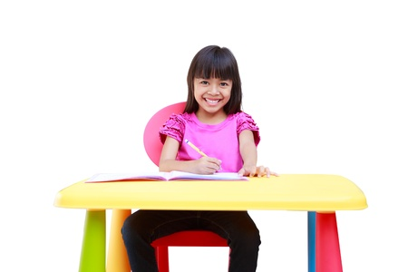 drawing table: Smiling little asian girl writing on the desk, Isolated over white with clipping path