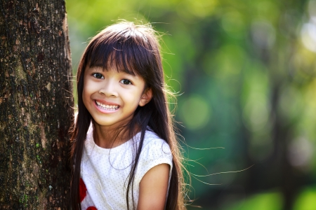 portrait background: Cute little girl smiling in a park close up