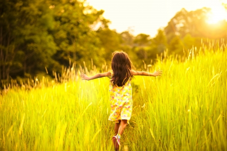 children: Little girl running on meadow with sunset Stock Photo