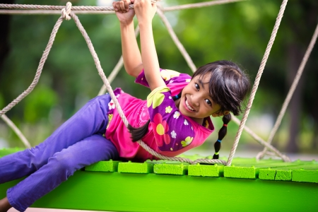 Happy little asian girl on the playground, Outdoor portrait photo
