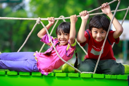 children at playground: Ni�o asi�tico feliz jugando juntos en el patio