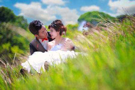 Portrait of romantic teenage couple sitting in green grass photo