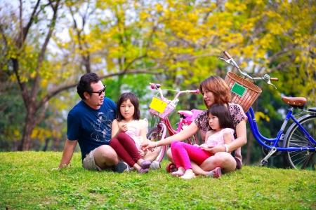 familia en jardin: Asia miente al aire libre de la familia que es juguetona y sonriente, retrato Outddor
