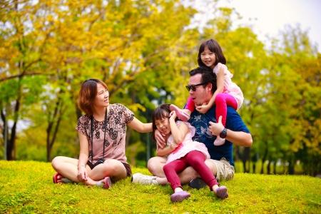アジアの家族の遊び心と笑みを浮かべて、アウトドアされて横になっている Outddor の肖像画