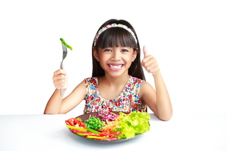 children eating: Little asian girl with vegetables food, Isolated over white