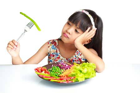 sad children: Little asian girl with expression of disgust against broccoli, Isolated over white