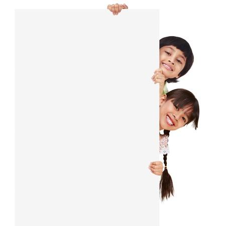ni�os sosteniendo un cartel: Los ni�os que presentan con un tablero blanco, aislado en blanco Foto de archivo