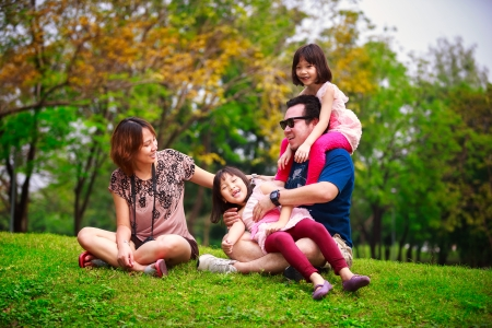 Family lying outdoors being playful and smiling, Outddor portrait photo