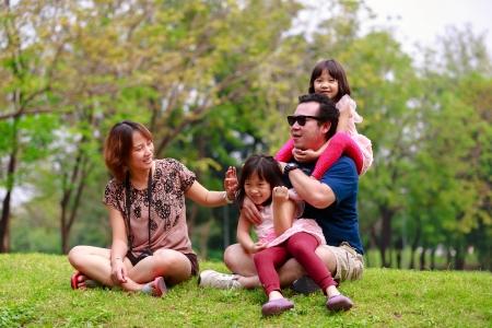 family picnic: Familia asiática feliz jugando juntos en un parque