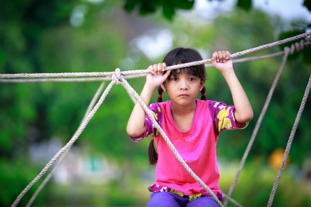 Sad little asian girl sitting alone on a playground, Outdoor photo