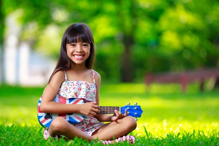 Little asian girl sitting on grass and play ukulele, Outdoor portrait photo