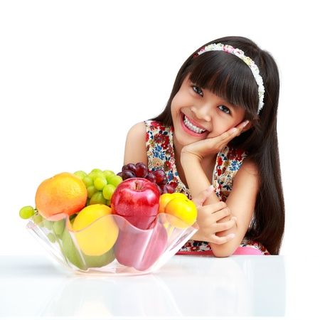 Happy little asian girl sitting on the table with plate of fruit, Isolated on white photo