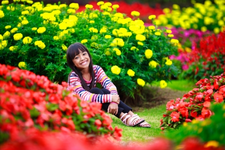 Smiling little asian girl sitting on flower field, Outdoor portrait photo