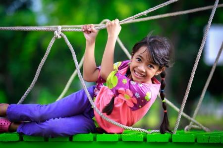 niños jugando en el parque: Feliz niña asiática en el parque infantil, retrato al aire libre Foto de archivo