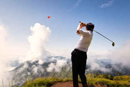 Young asian businessman hit golfball to flag on the cloud in the sky photo
