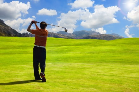Golfer driving golf ball on beautiful golf course with clear blue sky in the mountains photo