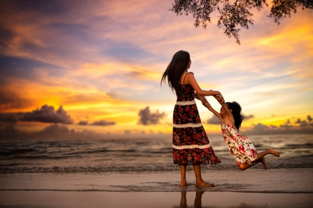 Mother playing with her daugher on the beach in evening Stock Photo