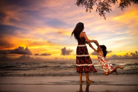 mutter: Mutter spielt mit ihre Tochter am Strand in Abend