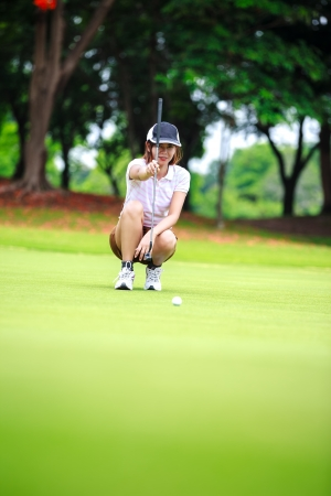 Female golf player with putter squatting to analyze the green at golf course photo