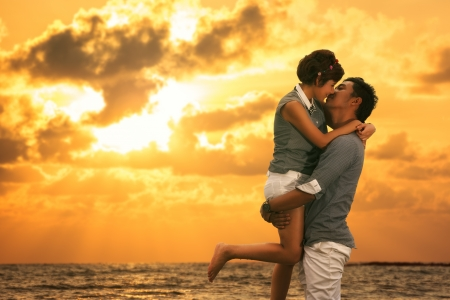 若いアジアの恋したカップルに滞在し、日没のビーチでキス