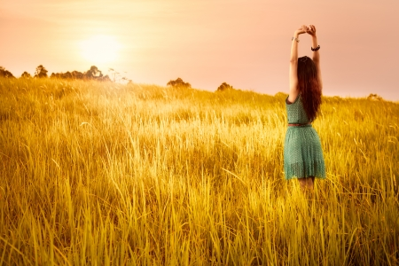 sunrise field: Happy young asian woman standing in meadows with sunset
