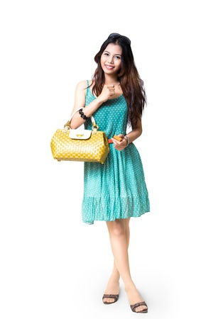 Young asian woman holding handbag, Isolated over white with clipping path photo