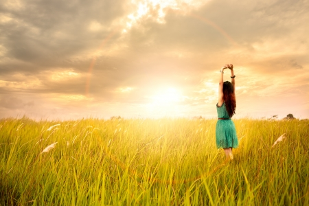 field sunset: Happy young asian woman standing in meadows with sunset