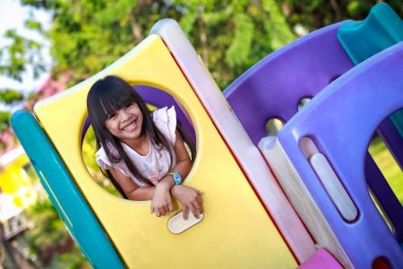 ni�o escalando: Sonriente ni�a asi�tica le gusta jugar en un parque infantil Foto de archivo