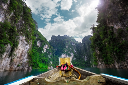 thai dam: Boat on green Lake with perfect sky at Ratchaprapa dam, Khaosok National Park, Thailand