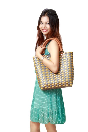 Young asian woman holding handbag, Isolated over white photo