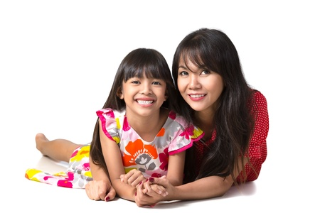 Happy mother and daughter laying on the floor, Isolated over white photo