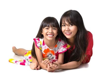 Heureuse mère et sa fille, portant sur le plancher, isolé sur blanc