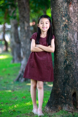 Happy young asian girl standing near a tree in a park photo