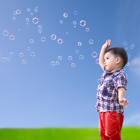 Baby little asian boy standing against blue sky with soap bubbles photo