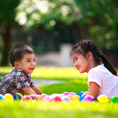 Two children, big syster and her young brother are laying on green grass and smile Stock Photo