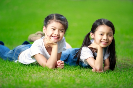 Two little asian girls laying on the green grass photo