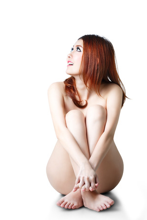 Young beautiful naked asian woman sitting on a floor photo