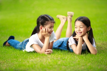 Two little asian girls laying on the green grass Stock Photo