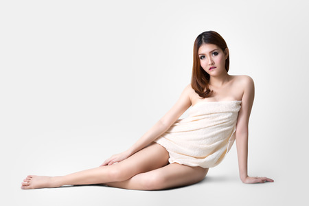 Asian woman wearing towel sitting on the floor, Isolated over grey color with clipping path photo