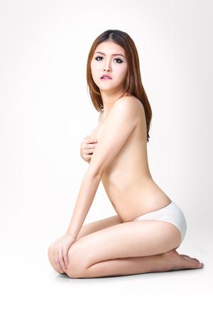 mujer desnuda sentada: Joven y bella mujer asi�tica desnuda sentada en el suelo, aislado en blanco
