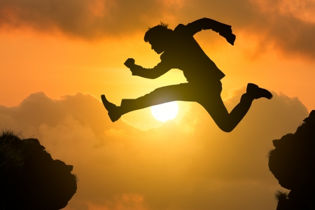 Silhouette businessman jump through the gap with sunset, Business competition concept photo